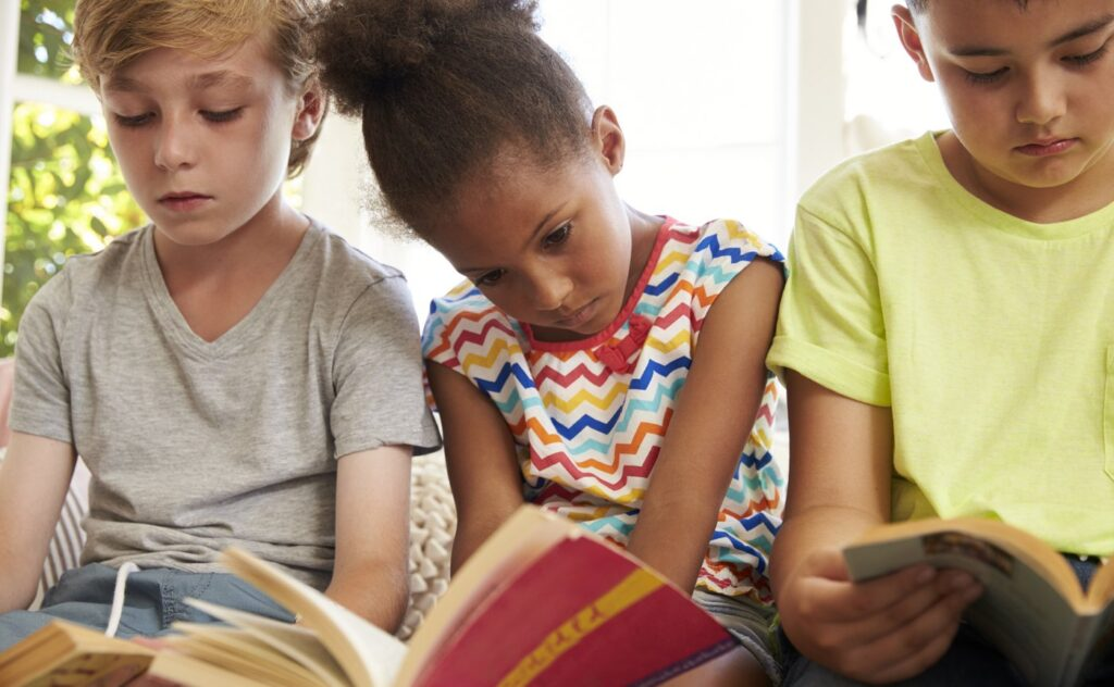 Close Up Of Children Reading On Window Seat