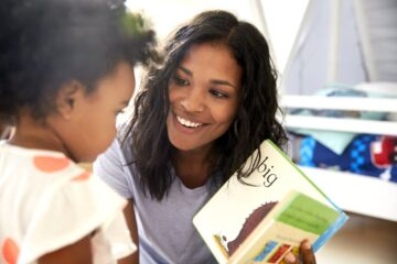 Mother and toddler daughter reading a baby board book