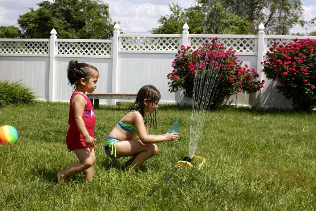 Sprinkler fun on the grass in the backyard